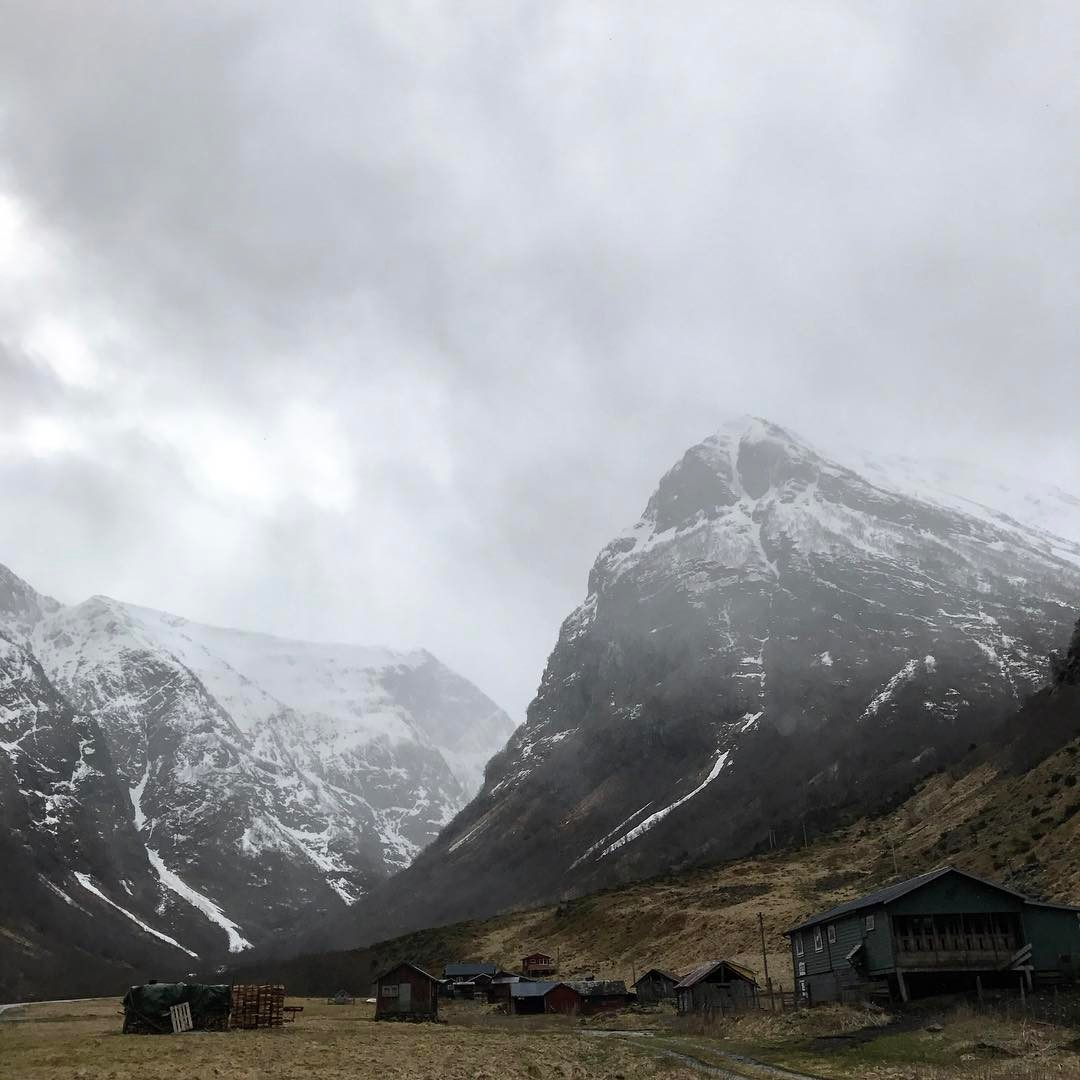 snowy mountains with shacks in foreground